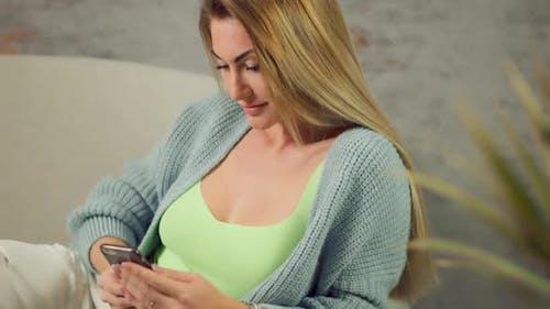 Nahaufnahme Blonde Frau nutzt Mobiltelefon, um zu Hause in den sozialen Medien zu chatten