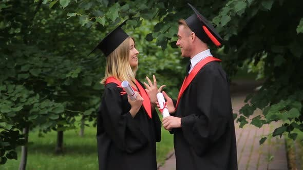Cover Image for Excited Smiling Graduates Holding Diplomas and Talking About Future in Park