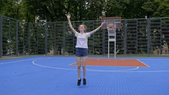 Thumbnail for Active Smiling Teenage Girl, Fashionable with Purple Hair, Jumping on Street Basketball Court with
