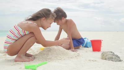 Two Kids Playing With Sand Toys
