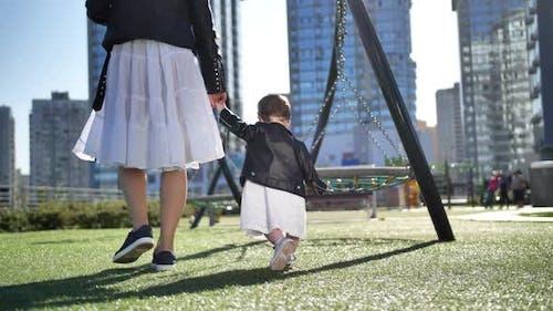 Little Girl Walking Holding Mom's Hand Outdoors