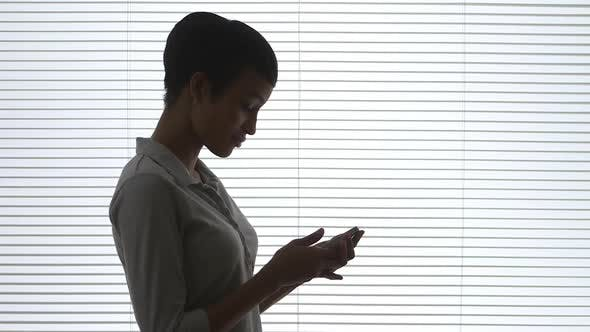 Thumbnail for Black business woman using mobile phone