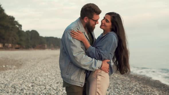 Bearded Man Is Kissing Tenderly Fragile Beloved Woman on Beach in Sunset Time