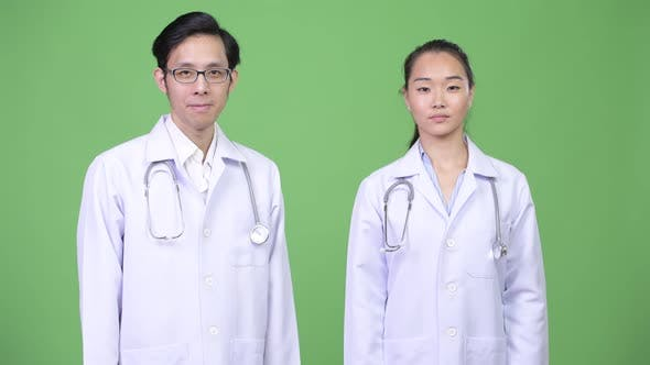 Young Asian Couple Doctors Giving Thumbs Up Together