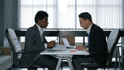 Two Young Businessman Talking at Desk in Office