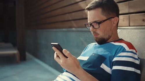 Mann mit einem Telefon in einer Lounge.