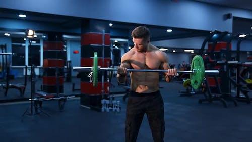 Sportlicher Mann im Fitnessstudio, der mit Langhantel trainiert. Bodybuilder mit perfektem Körper.