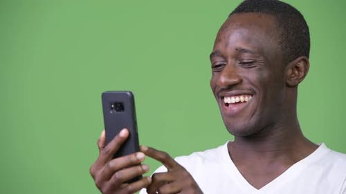 Young African Man Using Phone Against Green Background