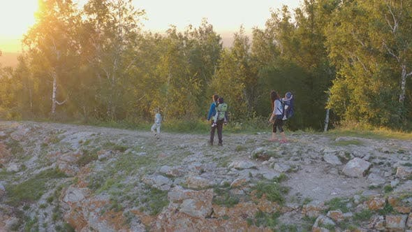 Thumbnail for Young Parents with Three Children Walk Along a Mountain Path at Sunset