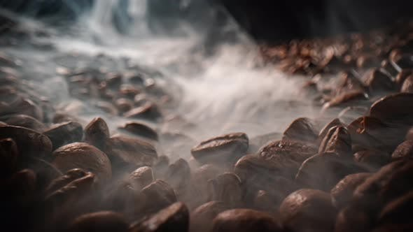 Close Up of Seeds of Coffee. Fragrant Coffee Beans Are Roasted Smoke Comes From Coffee Beans.