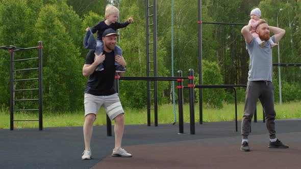 Thumbnail for Fit Caucasian Dads Doing Squats with Kids on Shoulders at Outdoor Gym