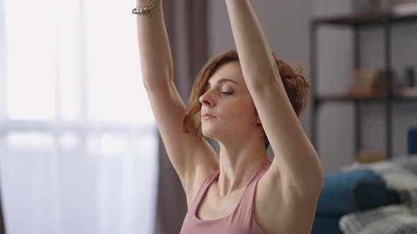 Morning Exercises and Workout for Stretching Woman is Sitting on Floor in Apartment Doing Exercises