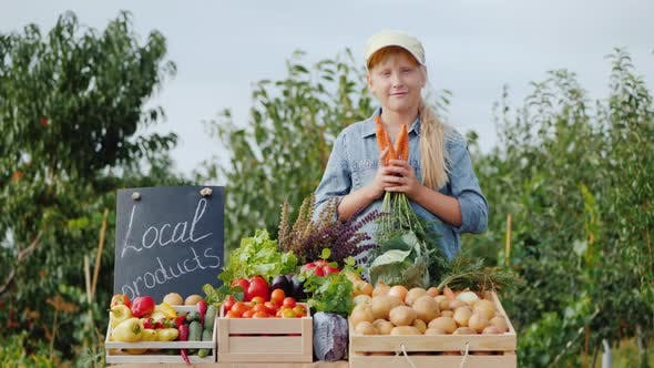Thumbnail for Little Farmer Girl at the Counter with Vegetables, Holding a Carrot