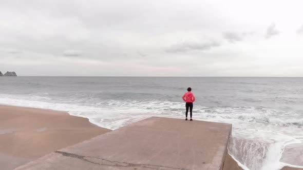 Camera follows young female running to edge of pier, admiring with beautiful sea landscape