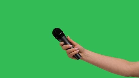 Female Hand Holding Microphone Against Background Green Screen Chroma Key