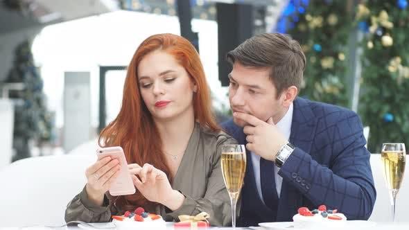 Ein verliebtes Paar bei romantischem Date im Restaurant. Entdecke das Online-Menü auf dem Smartphone von Rothaarig