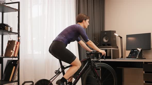 Woman is cycling on stationary bicycle. Indoor cycling.