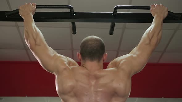 Thumbnail for Bodybuilder with perfect muscular body doing pull-ups, preparing for competition