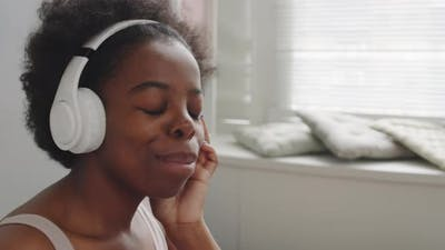 Young Black Woman Dancing to Music in Headphones in Bed