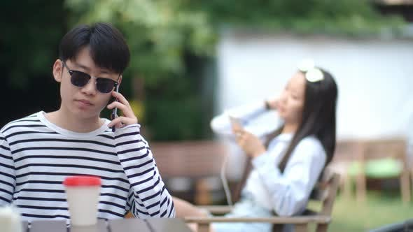 Thumbnail for Asian Teenager Speaking on Cell Phone at Cafe Table Outdoors