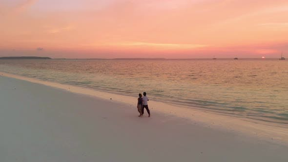 Thumbnail for Couple on vacation walking on exotic beach with romantic dramatic sky at sunset