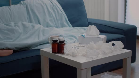 Woman with Virus Disease Resting in Blanket on Sofa