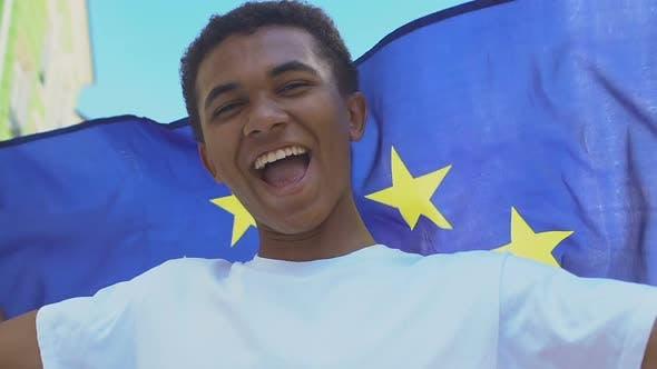 Happy Afro-American male teenager waving EU flag