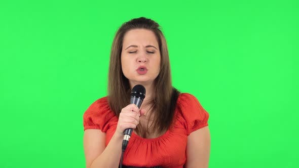 Thumbnail for Portrait of Cute Girl Is Singing Into a Microphone and Moving To the Beat of Music. Green Screen