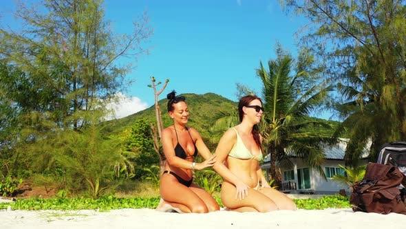 Thumbnail for Young Smiling Ladies on Vacation Having Fun at The Beach on Clean White Sand and Blue