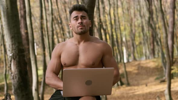 Thumbnail for Strong Naked Torso Guy Sits In An Autumn Park With Laptop In His Hands.