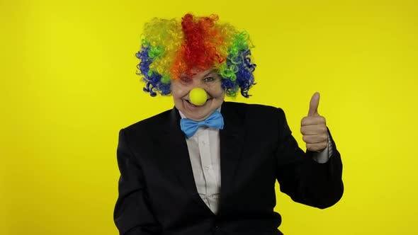 Thumbnail for Senior Woman Clown in Wig Having Fun, Smiling, Waves Her Hands, Show Thumb Up