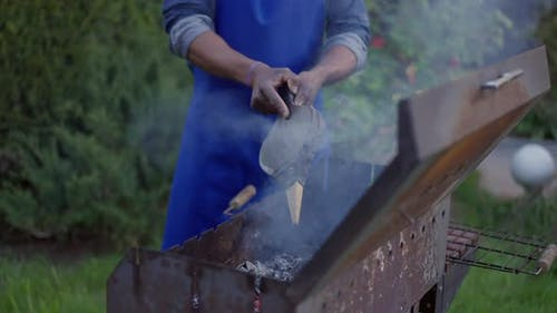 Unrecognizable African American Young Man in Apron Blowing Bbq Smoke Outdoors on Summer Day