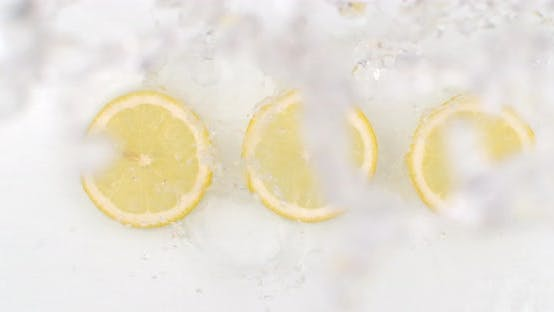 Thumbnail for On a White Background, a Splash of Water Falls on Three Slices of Lemon in Slow Motion