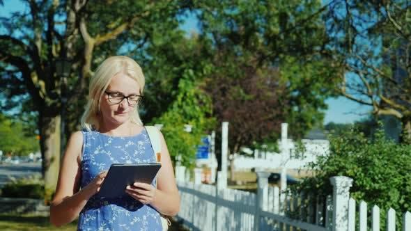 Женщина ходит по улице маленького американского города, смотрит на путь на планшет