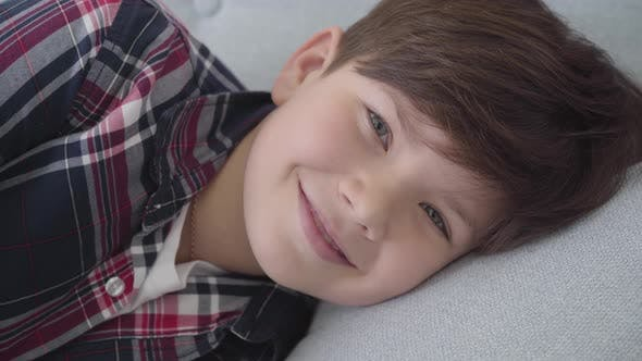 Thumbnail for Close-up of Caucasian Boy with Brown Hair and Grey Eyes Looking at Camera and Smiling. Happy Child