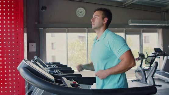 Thumbnail for Side View at Young Man Running on Treadmill at Gym, Slow Motion