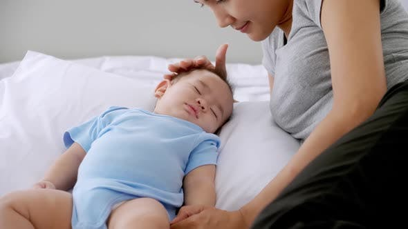 Sleeping little baby with young mother on bed.