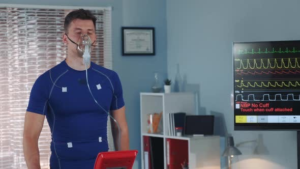 Thumbnail for Fit Athlete in Oxygen Mask Walking on Treadmill with Electrodes Connected on Him
