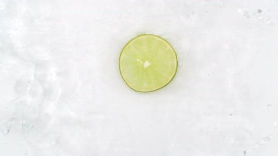 Thumbnail for On a White Background Cut Into Slices of Lime Sprinkled with Water Spray. Juicy Fresh Lime in Slow