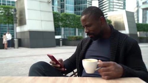 Handsome Black Man Is Reading News in Smartphone, Sitting on Open Terrace of Street Cafe with Coffee