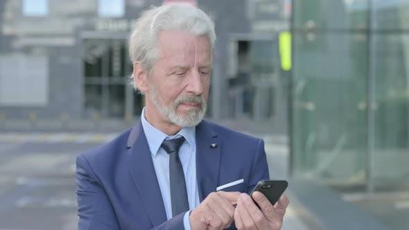 Old Businessman Using Smartphone Outdoor