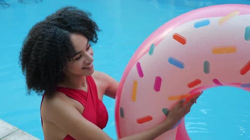 Close Up View of Playful African Model Play Throw Up Inflatable Donut in Mid-air Laughing Looking at