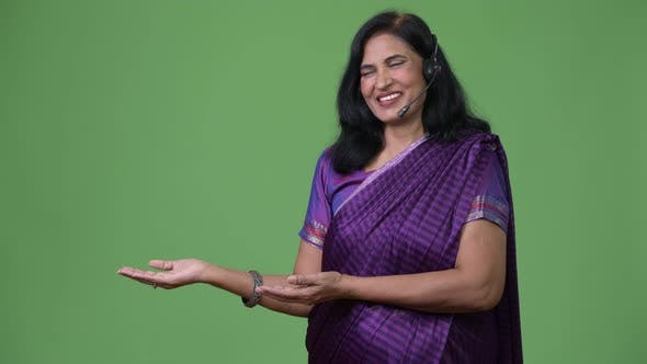 Thumbnail for Mature Happy Beautiful Indian Woman As Call Center Representative Smiling While Showing Something