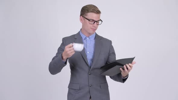 Thumbnail for Young Businessman Drinking Coffee While Reading Book with Eyeglasses