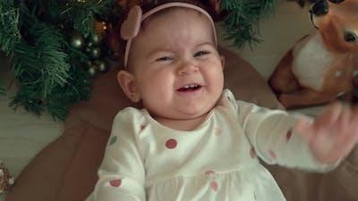 Happy Child Lies Near the Christmas Tree