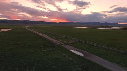 Flying alongside dirt road during colorful sunset in Star Valley Wyoming