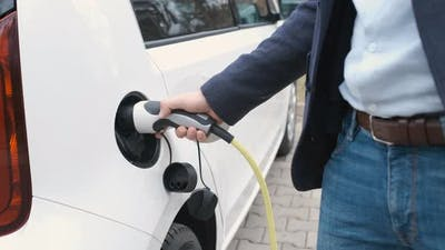 Man Coming to the Electric Car and Plugging in a Charging Cable