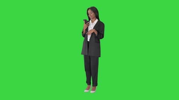 Thumbnail for Smiling Black Woman Texting on Her Cell Phone on a Green Screen, Chroma Key.