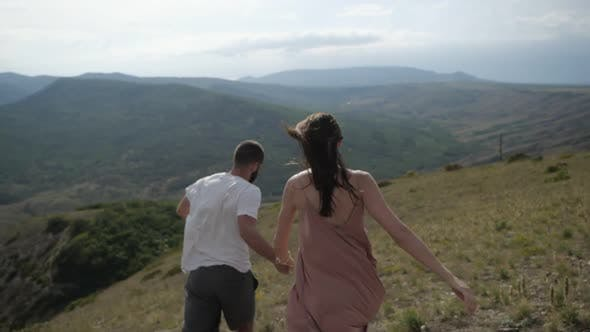 Thumbnail for The Happy Young Couple Holding Hands Runs From the Mountain.
