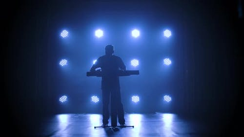 Musician Silhouette Playing on Synthesizer Piano Keyboard on Stage in a Dark Studio with Smoke and